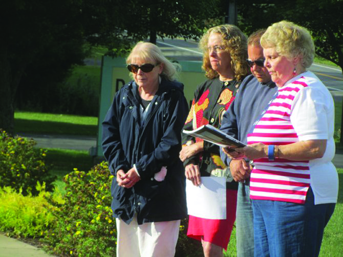 Elaine Lostumbo (right) leads a small remembrance memorial service at the DeWitt 9/11 memorial in 2012.