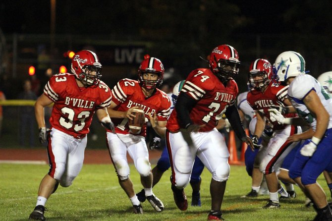 Baldwinsville quarterback Gage Blasi (12) sets off on an option play, flanked by fullback Caleb Carter (33) and lineman Jakeith Jackson (74), in Friday nght's game against Cicero-North Syracuse. Blasi and the Bees would go on to beat the Northstars 34-27.