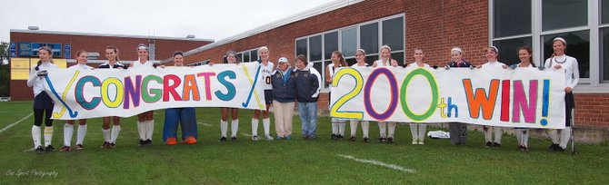 Cazenovia field hockey players unveil a banner congratulating head coach Lorraine Scheftic (middle) after  she won her 200th career game Friday afternoon at Burton Street Elementary School, the Lakers defeating Weedsport 2-0.