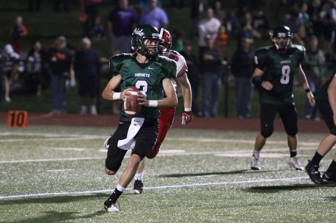 Fayetteville-Manlius quarterback Jake Wittig (3) scrambles out of the pocket and finds time to throw the ball downfield in Friday night's game against Baldwinsville. Wittig was 12-for-17 for 229 yards and four touchdowns as the Hornets outscored the Bees 49-37.