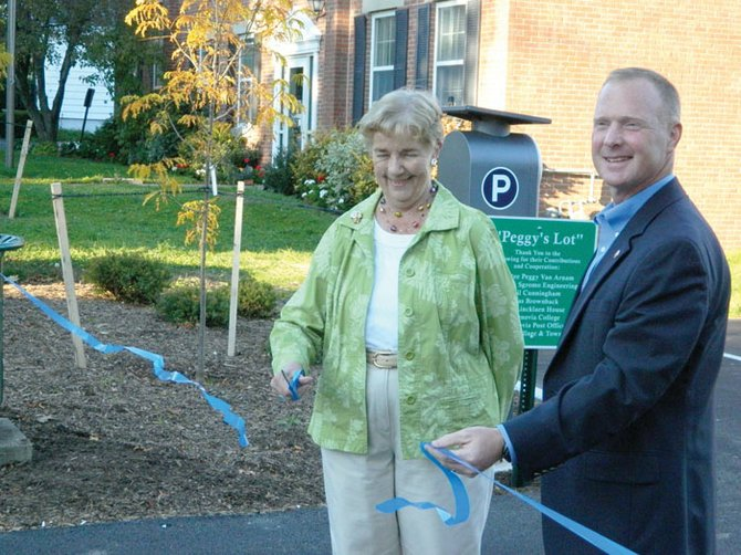 "Peggy Van Arnam, left, cut the ceremonial ribbon last Friday, Sept. 27, to officially open the new Lincklaen Street village parking lot. Mayor Kurt Wheeler, right, unveiled the sign that formally dedicated the lot as ""Peggy's Lot"" in honor of Van Arnam's dedicated work as a trustee to help the lot come to fruition."