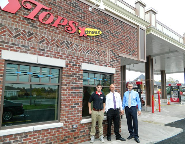 Tops store manager Joe Rizzo, far right, assistant store manager Rod Smith, middle, and fuel station general manager David Johnson pose in front of the nearly completed Tops gas station in the Town and Country Plaza. The station will officially open at 8 a.m. Wednesday, Oct. 9.