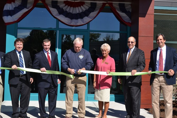 Mayor Marty Hubbard (center) cuts the ribbon to celebrate the grand opening of the net-zero energy consumption new village hall in Skaneateles.
