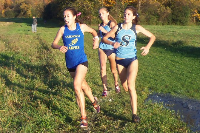 Skaneateles girls cross country runners Liz Dwyer and Madeline Adams follow Cazenovia's Jeanette Cudney around one of many slippery turns at Tuesday's meet, a 24-31 Skaneateles victory. Dwyer eventually finished second to Kaitlyn Neal in the meet, with Adams in fourth place.