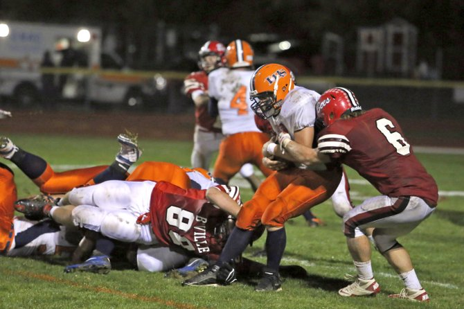 Baldwinsville defenders Kevin Carson (88) and Cole Burchill (6) combine to slow up Liverpool's Pat Twum on a running play in Friday night's game. The Bees led 24-10 at halftime, only to see the Warriors come back and prevail 31-24.