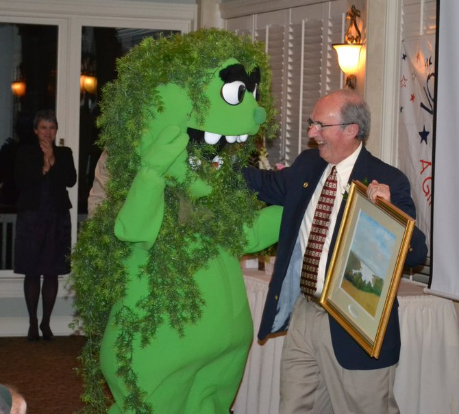 After accepting the Citizen of the Year award, Bob Werner is greeted by 'Milford the milfoil,' a surprise visitor at the award dinner held at Skaneateles Country Club on Oct. 17.