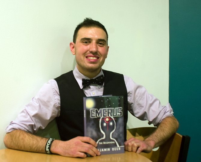 """Benjamin Deer, of Guilderland, holds a copy of his newly released book """"Emerus: The Beginning,"""" which is the first installment of a planned adventure fiction series."""