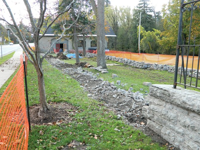 The rocky ditch, pictured above, is where the historic Lakeland Park wall usually sits. The wall, built about 1890, has been dismantled rock-by-rock and moved back into the park, visible at right, while local contractor Mike Walker works to shore up and reconstruct the structure.