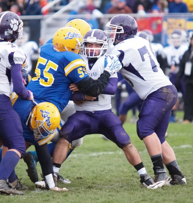 Cazenovia linebacker Hayden Polhamus (55) makes a hard hit on Cortland running back Zach Whelan in Saturday's Class B playoff game at Buckley-Volo Field. Polhamus and the Lakers' defense held the Purple Tigers to a single first down the entire game in a 43-0 shutout.