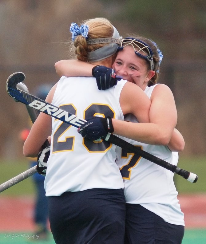 Cazenovia field hockey teammates Sarah Willard (20, left) and Rachel McLaughlin (17) share a hug after one of McLaughlin's first-half goals in the Lakers' 2-0 win over Hoosick Falls Saturday in the Class C regional finals at Cicero-North Syracuse's Bragman Stadium.