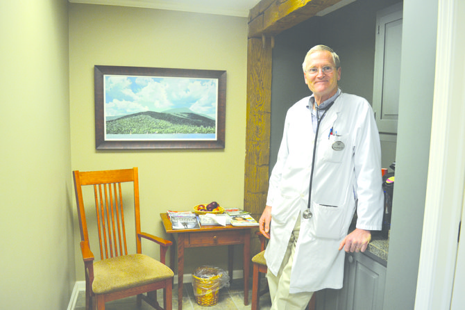 "Dr. Chris Stringer stands in the waiting room at his private practice facility in Manlius. ""The idea is that people don't wait here very long,"" he said, smiling."