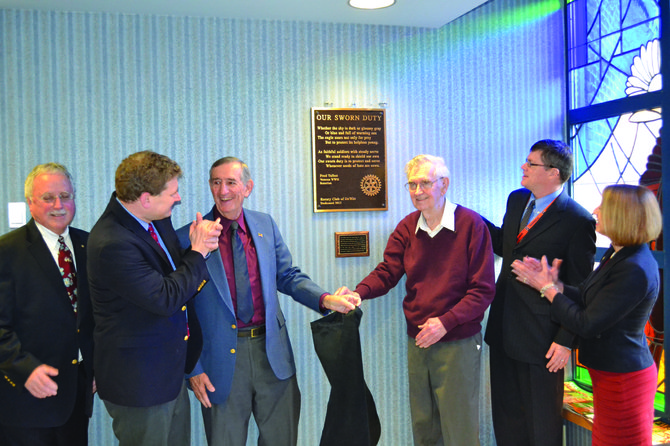 "Mel Rubenstein (center left) and Fred Talbot (center right) remove the cover to reveal the plaque that bears Talbot's poem, ""Our Sworn Duty,"" at the VA Hospital on Nov. 8. They are surrounded by DeWitt Rotarians, including Congressman Dan Maffei."