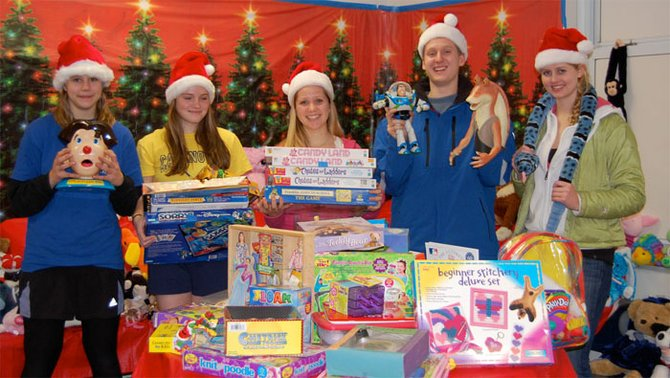 Student volunteers pose with toys at a previous Gently Used Toy Shop event.