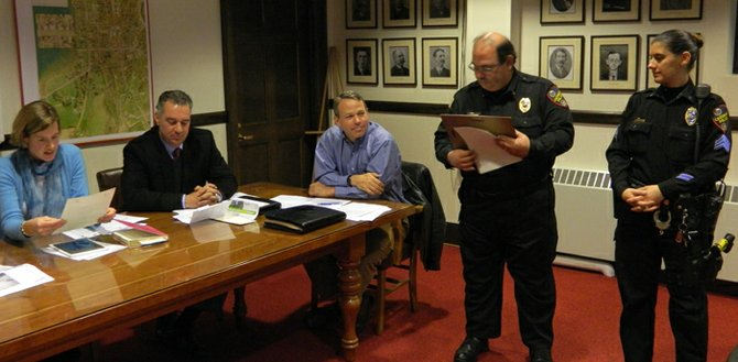 Cazenovia Police Chief Michael Hayes, second from right, awards Sgt. Karen Zaleski, far right, a letter of citation during the Nov. 4 village board meeting. Village Trustee and Police Commissioner Amy Mann, far left, reads the citation out loud while trustees Jim Joseph and Fritz Koennecke look on.