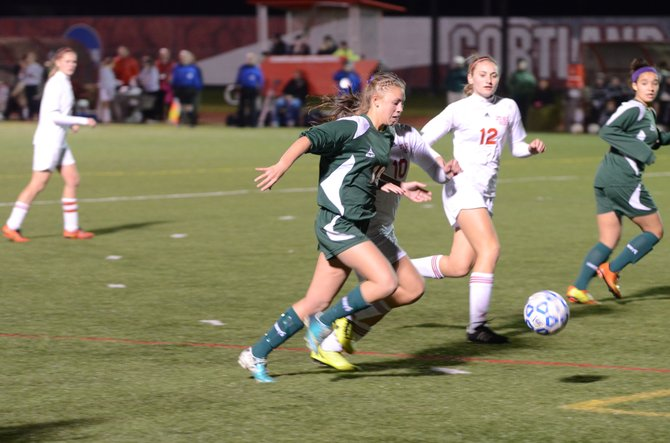 Marcellus senior midfielder Emma Blystone (19) sprints past two Center Moriches defenders with the ball late in Saturday's state Class B semifinal at SUNY-Cortland, where the Mustangs would defeat the Red Devils 2-0.