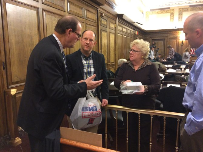Albany County Legislator Mary Lou Connolly, D-Guilderland, on Tuesday, Nov. 12, talks to, from left, Mike Levy, of the American Chemistry Council, and George Braddon, president of Commodore Plastics, about the proposed ban on Styrofoam usage at chain food establishments in the county. The ban was passed later that night.