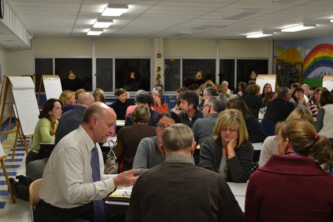 Community members discussed strategies for dealing with pressures facing the Skaneateles school district at a community forum held Wednesday. ABOVE: Board of Education Vice President Thomas Lambdin (left) works with a table to discuss ideas.