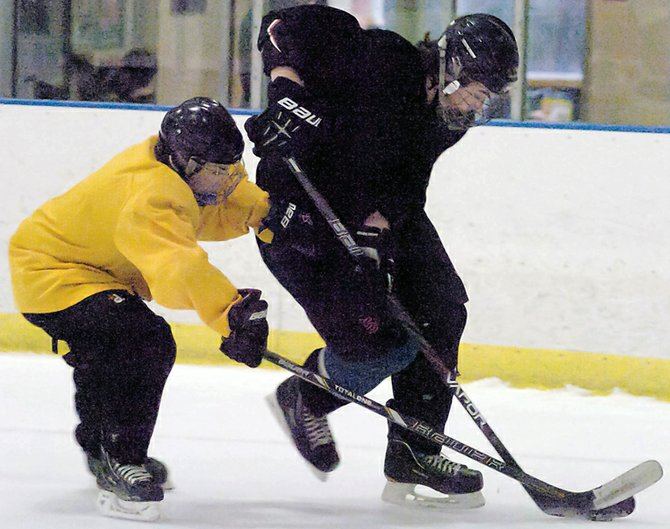 Bethlehem defenseman Robert Lemieux, right, battles for the puck during a recent hockey practice at the Bethlehem Area YMCA. The Eagles begin their season at this weekend's Shaker/Colonie Thanksgiving Tournament at the Albany County Hockey Facility.