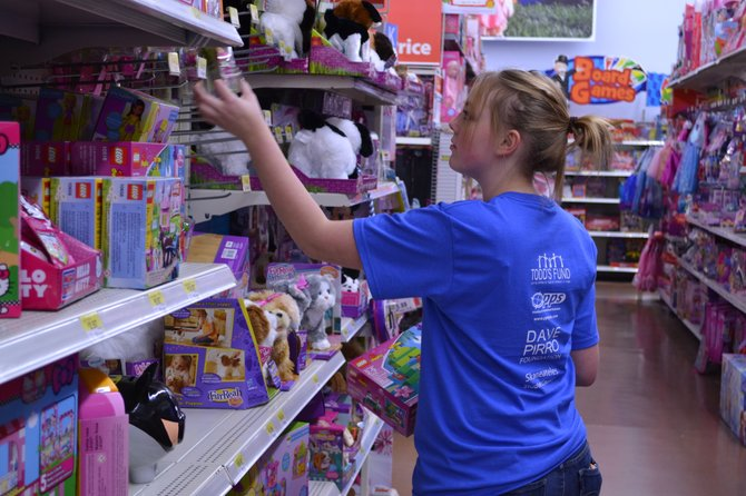 Maddy Dubach looks at toys to purchase and donate to charity during Skaneateles Middle School's annual Holiday Shopping Spree at Wal Mart.