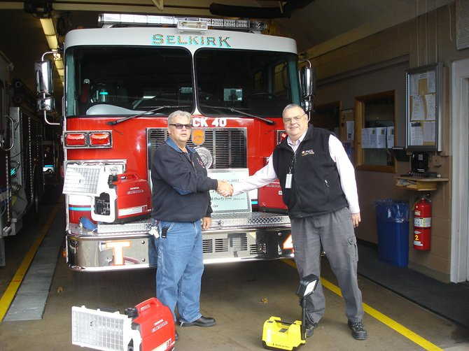 Selkirk District Fire Chief Bill Asprion (left) thanks Bill Clancy, plant manager at the Bethlehem Energy Center, for funding new portable lighting.