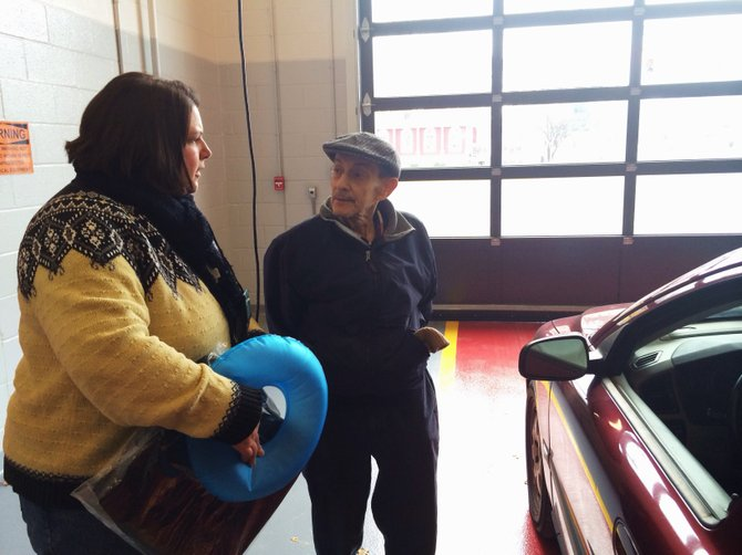 CarFit volunteer Donna Stressel recommends seat cushion alternatives to Ron Bratspis, an Atria Crossgates resident, who uses an inflatable doughnut. Bratspis was one of approximately 15 people receiving tips.