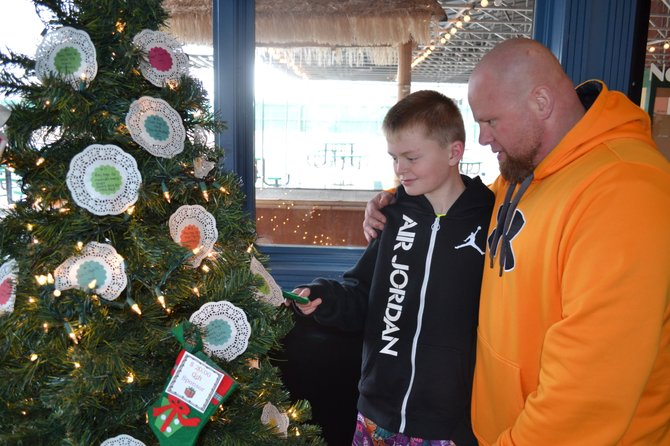 "Gannon Abreu, 13, and his father Danny Abreu pick a paper ornament off of the Tillie's Touch Christmas Wish Tree on Dec. 1. The Abreus, who live in East Syracuse, are ""adopting"" a local child for Christmas this year."