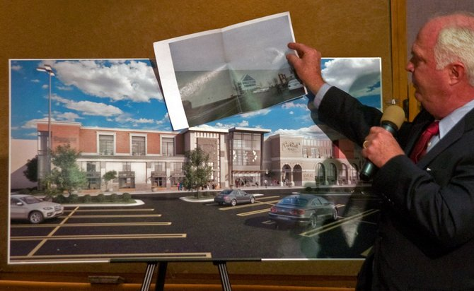 Robert Sweeney, a lawyer representing Crossgates Mall, on Wednesday, Dec. 18, shows a comparison between the current building facade and what it will look like after an addition and exterior renovations are completed.