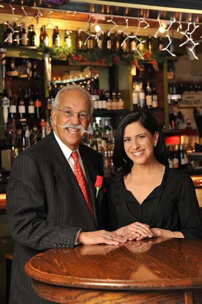LeGrande Serras and his daughter, Aliki Serras, pose in the bar area of Reel Seafood Co. as Aliki takes over the restaurant her father has owned and operated for the last 30 years.