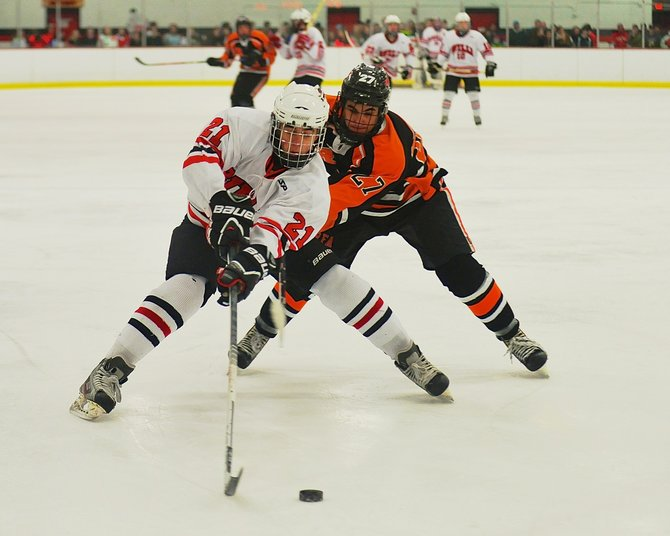 Baldwinsville forward Adam Tretowicz (21) chases down the puck, closely followed by Rome Free Academy's Jason Rutkowski (27), in last Tuesday's game. Despite an assist from Tretowicz, the Bees lost, 4-2, to the first-place Black Knights.