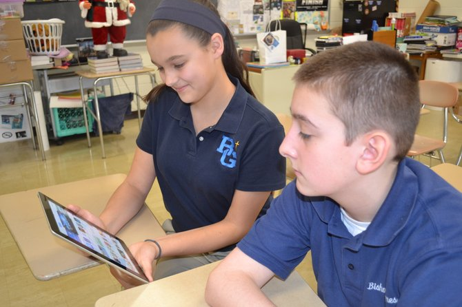 """Bishop Grimes seventh-graders Sarah Snavlin and John Wilbur use an iPad mini during class. """"It's kind of cool that you can just go on your iPad and pull up a book instead of having to go through your bag, grab your book and flip through the pages,"""" said Wilbur."""