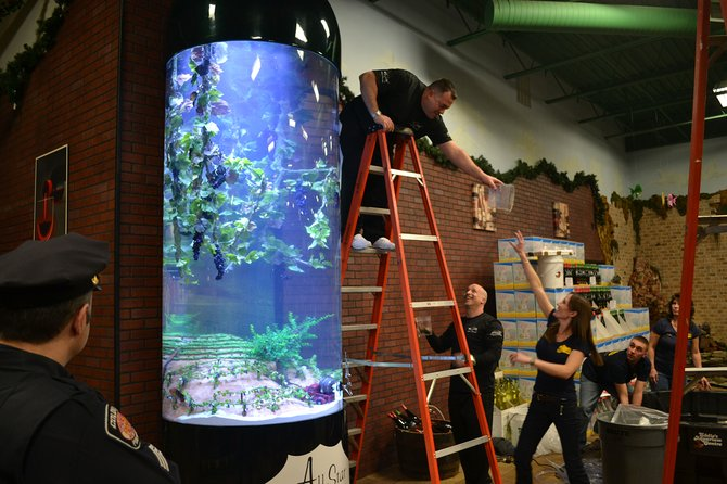 """A large crowd looks at All Star Wine and Liquor's new bottle-shaped fish tank at its Feb. 7 unveiling. The tank and the store will be featured on a March episode of the Animal Planet series, """"Tanked."""""""