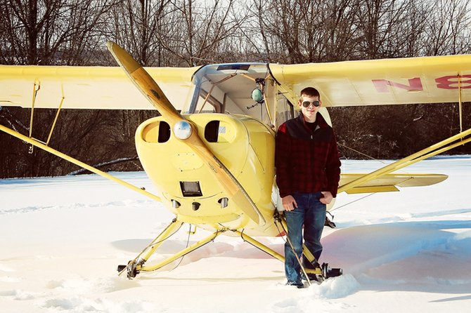 Hunter Havener poses with his father's 1946 Aeronca 7Ac Champ aircraft, in which he is learning to fly.