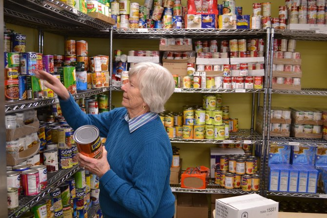 Volunteer Joan Tarolli organizes food at the Skaneateles Ecumenical Food Pantry.