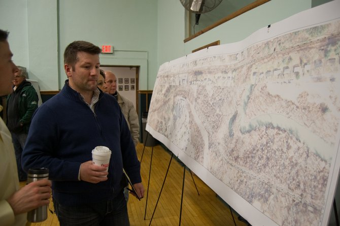 People look over an aerial image outlining where the third phase of the Albany County Rail Trail will be constructed before presentation on the project Thursday, Feb. 20.