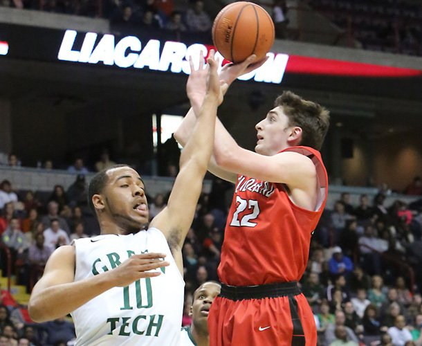 Guilderland's Andrew Platek, right, gets a shot off despite being defended by Green Tech's Jizziah Carr during Monday's Section II Class AA championship game at the Times Union Center.