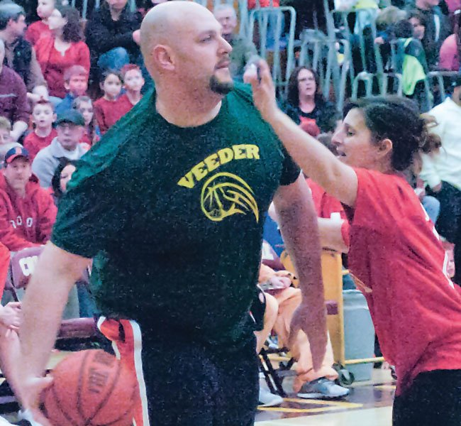 Veeder Elementary School teacher Matt Tarullo looks for a teammate to pass the ball to during last Friday's Amy Tisa Memorial Basketball Game.