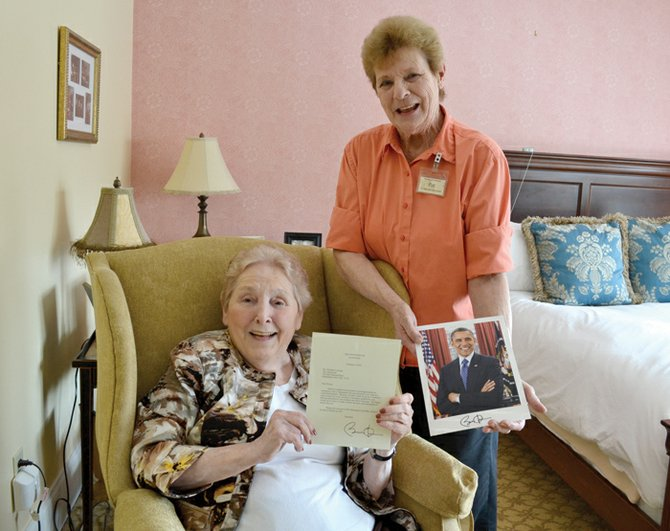 """Winnie"" Coleman and Patricia Campbell display the letter and signed photo sent to the Athenaeum by President Obama."