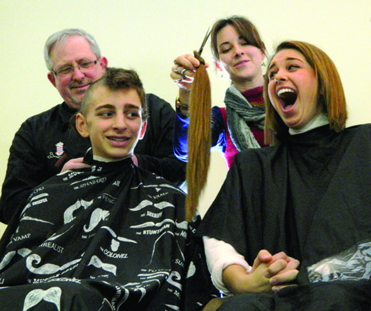 Stylist Lindsay Waltz shows teen Amara Kattrein a piece of hair she just cut in preparation for shaving all 23 inches of Kattrein's hair at the March 16 St. Baldrick's fundraiser in Cazenovia. Amara and her brother Hans, left, held hands as they got shaved.