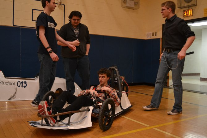 Senior Jake Regan (seated) and members of the high school technology club test out their Electrothon car. Regan has been constructing a carbon fiber frame for the car for a class project, which will make it lighter and more efficient.