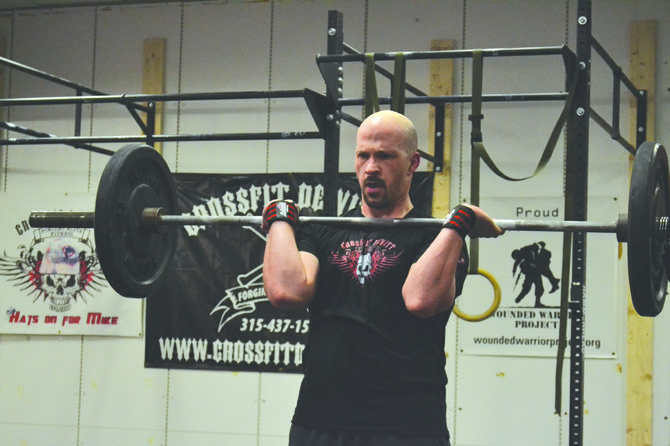 Steve Singer, of Syracuse, lifts 95 pounds while doing  bar facing burpees during a workout at CrossFit DeWitt on March 28.