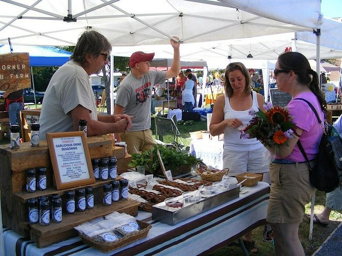 A vendor at a 2012 session of the Chestertown Farmers' Market describes his condiments and herbs to a shopper — who holds a bouquet of fresh cut flowers she purchased at the popular venue, which opens Wednesday June 18 for the 2013 season. The Triu-Lakes Business Alliance, sponsors of the market, have been lining up their events and schedules this week for the summer season. The Chestertown Farmers' Market has been lauded as an overwhelming success that's boosted commerce in northern Warren County, as well as strengthening social ties in town. The market features a wide range of produce, gourmet foods and handcrafted goods. The Alliance has meanwhile developed a series of themed events that have been remarkably popular and have helped enhance community spirit in the region.<br /> Courtesy photo