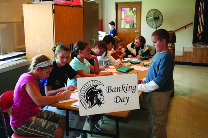 Jacob Keuler, right, makes a deposit during Banking Day at Minoa Elementary School in2009. High school business students get hands on experience running the program with the CORE Federal Credit Union and serving as mentors to younger students. Earlier this month, ESM High School's student-run credit union, the Spartan Branch, collected its millionth dollar deposited by students.