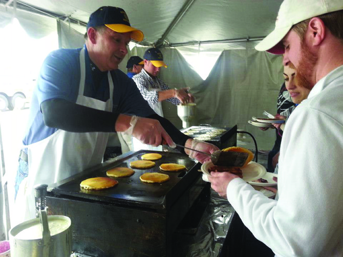 DeWitt Rotarian Dave Schneckenburger serves pancakes to hungry customers at the rotary club's Pancake Day in 2013. This year, the DeWitt Rotary Club is holding its 60th annual Pancake Day on May 10 at Shoppingtown Mall.
