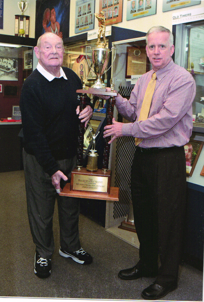 """The trophy is presented to Greater Syracuse Sports Hall of Fame member John Rathbun, right, by Bill LeMon, a member of """"The Coolican"""" organizing committee and longtime participant in the event. Rathbun and LeMon are both DeWitt residents."""