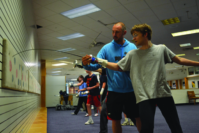 Lubo Kalpaktchiev grew up under the Iron Curtain and immigrated to the United States in 1999. Now he teaches students as young as 7 and adults who are well into retirement the fundamentals of fencing at his facility in Shoppingtown Mall, the Syracuse Musketeers Fencing Center. Pictured is Kalpaktchiev, helping Aaron Alexander, 20, of Syracuse, with his form during target practice.