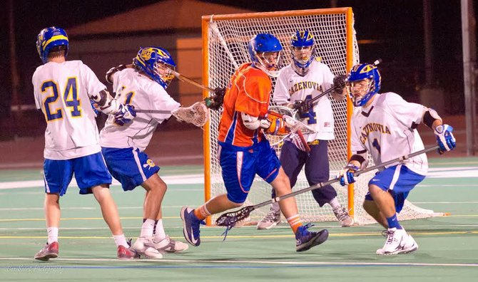 Cazenovia defenders Eli Mitchell (11) and Jay Hahn (1), flanked by Cole Willard (24), join goalie Trevor Cross in shutting down Penn Yan's attack in Wednesday night's state Class C semifinal. During the second half of the Lakers' 8-6 win, it held the Mustangs without a goal for more than 16 minutes.