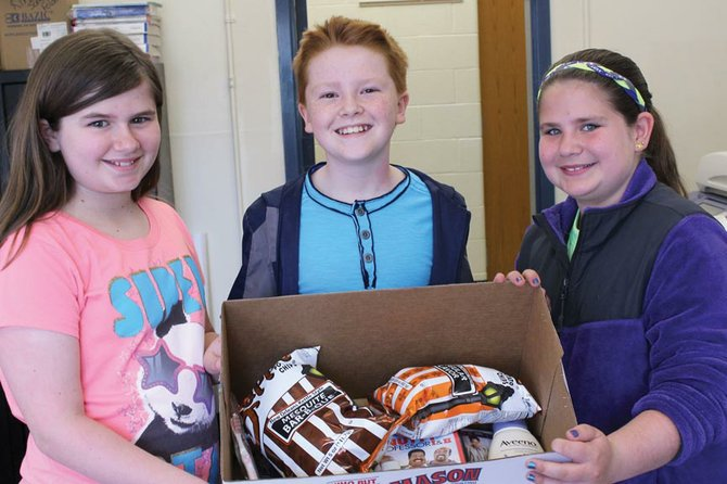 From left, Hailey Sweeney, Cameron Fletcher and Madison Olney display some of the items they have already collected to send to U.S. military troops to thank them for their service.