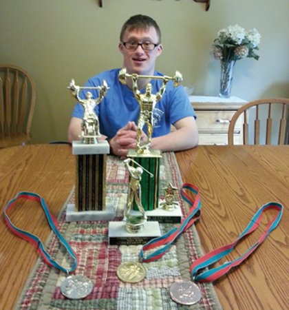 Cazenovia resident Ryan Goldacker, above, poses with just a few of the numerous medals and trophies he has won through the years competing in swimming, skiing, golf and powerlifting.