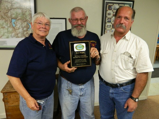 "The Nelson Town Board last week honored Erieville firefighter Bob Magee, center, for his milestone of 50 years of service with the Erieville Fire Department, and presented him a plaque in commemoration of the achievement. The board also applauded Jane Magee, left, Bob's wife, for her 38 years of service with the EFD, and for the fact that she was the first female firefighter in Madison County. ""I applaud them for their service,"" said Joe DeFrancisco, Madison County emergency services coordinator, right, who presented the plaque to Bob Magee at the Nelson Town Board's June 12 meeting."