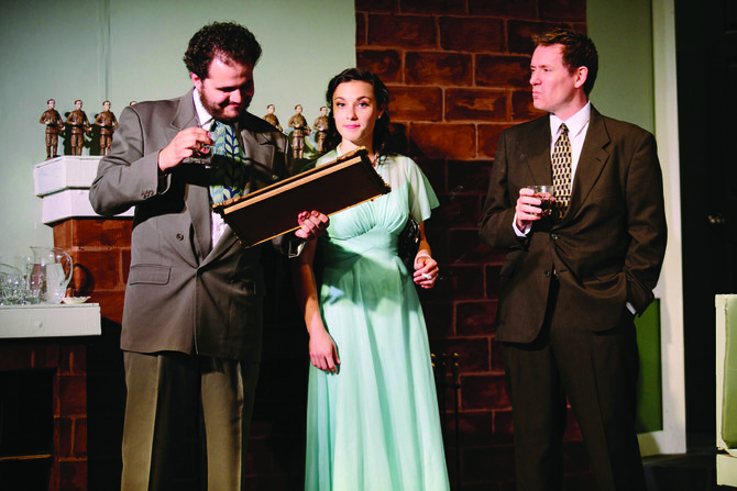"""Reading the rhyme: Vincent Randazzo as William Blore, Alicia Bronzetti as Vera Claythorne and Mark Allen Holt as Philip Lombard peruse the mantelpiece nursery rhymes which ends with the words that became the title of the play, """"And Then There Were None,"""" now running through June 28, at CNY Playhouse, in DeWitt's ShoppingTown Mall."""